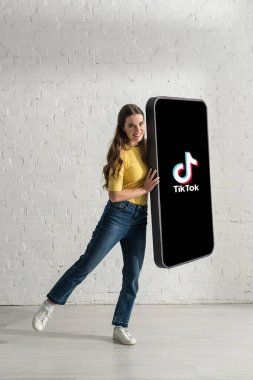 KYIV, UKRAINE - FEBRUARY 21, 2020: Beautiful girl smiling and looking at camera while holding big model of smartphone with TikTok app stock vector
