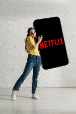 KYIV, UKRAINE - FEBRUARY 21, 2020: Smiling girl hugging big model of smartphone with netflix app at home
