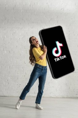 KYIV, UKRAINE - FEBRUARY 21, 2020: Attractive woman laughing while holding huge model of smartphone with TikTok app near white brick wall stock vector