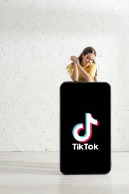 KYIV, UKRAINE - FEBRUARY 21, 2020: Smiling woman looking at big model of smartphone with TikTok app near white brick wall stock vector