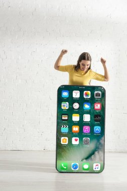 KYIV, UKRAINE - FEBRUARY 21, 2020: Positive girl looking at big model of smartphone with iphone screen while showing yeah gesture stock vector