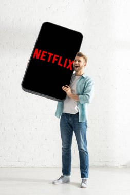 KYIV, UKRAINE - FEBRUARY 21, 2020: Excited man holding model of smartphone with netflix app near white brick wall stock vector