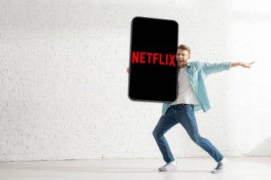 KYIV, UKRAINE - FEBRUARY 21, 2020: Cheerful man holding big model of smartphone with netflix app near white brick wall stock vector