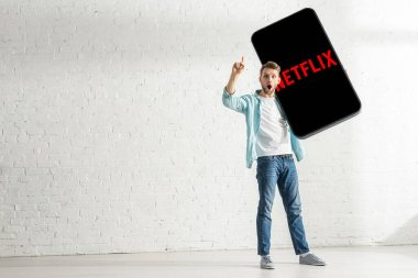 KYIV, UKRAINE - FEBRUARY 21, 2020: Shocked man having idea while holding big model of smartphone with netflix app at home stock vector