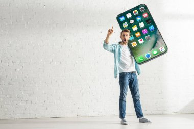 KYIV, UKRAINE - FEBRUARY 21, 2020: Excited man showing idea gesture while holding big model of smartphone with iphone screen stock vector