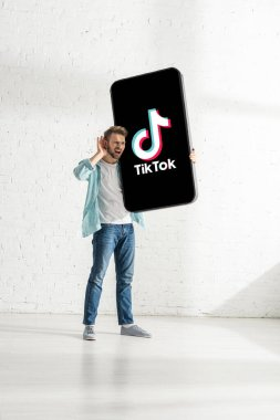 KYIV, UKRAINE - FEBRUARY 21, 2020: Young man with hand near ear holding huge model of smartphone with TikTok app at home stock vector