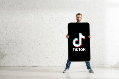 KYIV, UKRAINE - FEBRUARY 21, 2020: Handsome man holding big model of smartphone with TikTok app and smiling at camera stock vector
