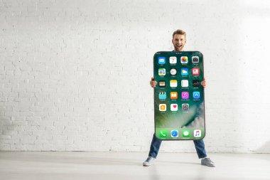 KYIV, UKRAINE - FEBRUARY 21, 2020: Cheerful man holding smartphone model with iphone screen near white brick wall stock vector