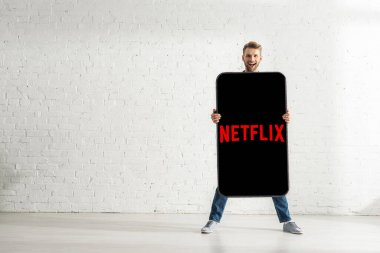 KYIV, UKRAINE - FEBRUARY 21, 2020: Handsome man smiling at camera while holding big model of smartphone with netflix app at home stock vector