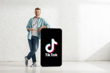 KYIV, UKRAINE - FEBRUARY 21, 2020: Handsome man pointing with finger at model of smartphone with TikTok app and smiling at camera stock vector