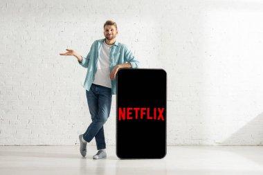 KYIV, UKRAINE - FEBRUARY 21, 2020: Smiling man showing shrug gesture near model of smartphone with netflix app stock vector