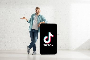 KYIV, UKRAINE - FEBRUARY 21, 2020: Smiling man showing confused gesture near big model of smartphone with TikTok app stock vector