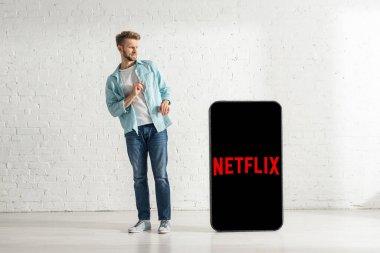 KYIV, UKRAINE - FEBRUARY 21, 2020: Scared man standing near huge model of smartphone with netflix app stock vector