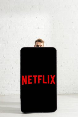 KYIV, UKRAINE - FEBRUARY 21, 2020: Man looking at camera near big model of smartphone with netflix app at home stock vector
