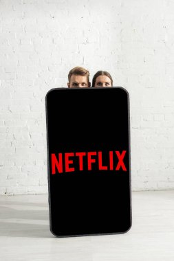 KYIV, UKRAINE - FEBRUARY 21, 2020: Couple looking at camera near huge model of smartphone with netflix app at home stock vector