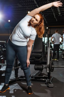 pretty, overweight girl warming up while doing side tilt exercise