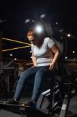 nadváha dívka ve sportovním oblečení školení na fitness stroje v tělocvičně