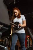 hezká, nadváha dívka přibírá na váze disk z fitness stroje