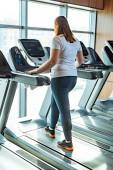 Fotografie rothaarige übergewichtige Mädchen trainieren auf Laufband im Fitnessstudio in Fensternähe