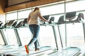 Fotografie Übergewichtiges Mädchen trainiert auf Laufband in Turnhalle gegen Fenster