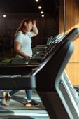 selektivní zaměření unavené dívky s nadváhou dotýkající se čela při běhu na běžícím pásu