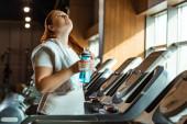 unavená nadváha dívka s ručníkem na rameni drží sportovní láhev a dívá se nahoru, zatímco stojí na běžícím pásu