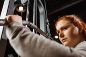 selektivní zaměření sebevědomé nadváhy dívka dělá rozšíření zbraní cvičení na fitness stroje