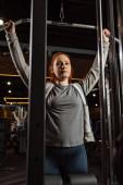 nadváha dívka dívá na kameru, zatímco dělá rozšíření zbraní cvičení na fitness stroje