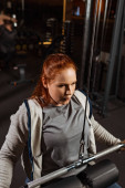 soustředěná nadváha dívka dělá rozšíření zbraní cvičení na fitness stroje