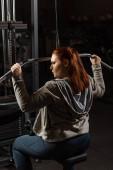 sebevědomí nadváha dívka dělá rozšíření zbraní cvičení na fitness stroje