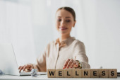 selective focus of happy businesswoman working with laptop at workplace with alphabet cubes with wellness word