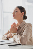 Photo beautiful businesswoman meditating with namaste gesture and closed eyes in office