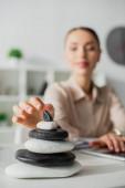selektivní zaměření podnikatelky pracující s notebookem na pracovišti s zen kameny