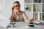 usmívající se podnikatelka sedící na pracovišti s zen kameny, smartphone a notebook