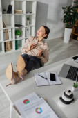 Photo beautiful young businesswoman procrastinating with feet on table in office
