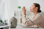 selektivní zaměření podnikatelky meditující s namaste gestem na pracovišti s Buddhovou hlavou a kadidlem