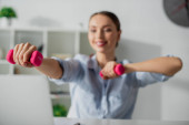 selective focus of happy businesswoman training with dumbbells at workspace