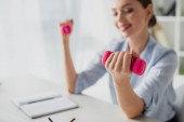 selective focus of happy businesswoman training with pink dumbbells in office
