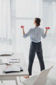 back view of young businesswoman training with dumbbells in office with documents and laptop