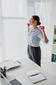beautiful businesswoman training with dumbbells in office with documents and laptop