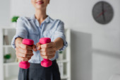 cropped view of businesswoman training with pink dumbbells in office