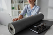 selective focus of young businesswoman working on laptop at workplace with yoga mat, notepad, smartphone and eyeglasses