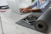 selective focus of businesswoman working on laptop at workplace with fitness mat, notepad, smartphone and eyeglasses