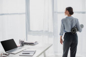 back view of businesswoman holding yoga mat at workspace with laptop and notepad