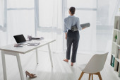 back view of young businesswoman holding yoga mat at workspace with laptop