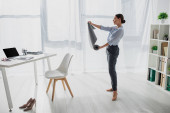 beautiful young businesswoman holding yoga mat in office