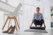 happy young businesswoman laying yoga mat on floor in office