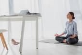 mladá podnikatelka cvičit jógu v lotosové pozici s gyan mudra na podložce v kanceláři