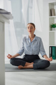 attractive businesswoman practicing yoga in lotus position with gyan mudra on mat in office