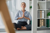 Photo selective focus of businesswoman practicing yoga in lotus position with namaste gesture on mat in office
